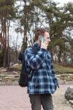 Grabb med en ryggsäck som talar på telefonen Arkivfoton