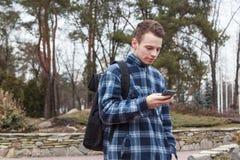 Grabb med en ryggsäck som talar på telefonen Arkivbild