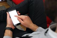 Grabb med ett skägg som hemma ser en smartphone royaltyfri bild