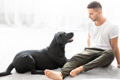 Grabb med hans hund som hemma sitter att spela royaltyfri fotografi