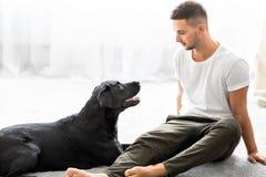 Grabb med hans hund som hemma sitter att spela arkivfoto