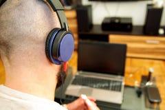 Grabb med lyssnande musik för hörlurar på bärbara datorn i vardagsrum Royaltyfria Foton