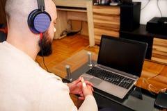 Grabb med lyssnande musik för hörlurar på bärbara datorn i vardagsrum Arkivfoton