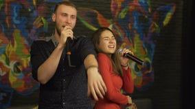 Grabb och en flicka som sjunger i en karaokeklubba långsam rörelse stock video