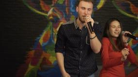 Grabb och en flicka som sjunger i en karaokeklubba långsam rörelse arkivfilmer