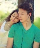 Grabb och flicka för tappningfotopar i hörlurar som tycker om musik Royaltyfri Bild
