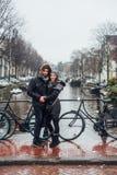 Grabb och flicka i gatan i regnet arkivfoto