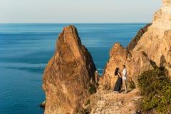 Grabb och flicka på havet som kramar på kanten av klippan royaltyfria foton