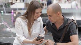 Grabb och flicka som sitter i gallerian på bakgrunden av springbrunnen som diskuterar foto på telefonen och skrattet lager videofilmer