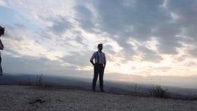 Grabb- och flickaställning på solnedgången stock video