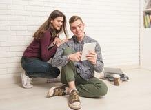 Grabb- och flickastudenter sitter på golvet arkivbilder