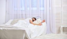 Grabb på lugna framsida som sover på vitark, kudde Ta sig en tupplur och siestabegreppet Macho med skägget som sover och att kopp Arkivfoton