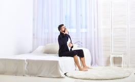 Grabb på sömnig framsida som gäspar i morgon Väckande begrepp Mannen i ämbetsdräkt sitter på säng, vitgardiner på bakgrund macho Royaltyfri Foto