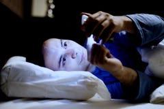 Grabb som använder hans mobiltelefon i sängen royaltyfri foto
