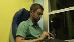 Grabb som använder hans mobiltelefon, medan resa till en annan destination på nattdrevet stock video