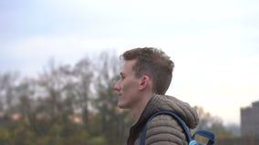 Grabb som går i molnig stad Stilig ung caucasian man som bär det tillfälliga omslaget som går vidare vägen arkivfilmer
