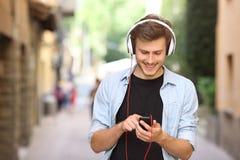 Grabb som går och använder en smart telefon med hörlurar royaltyfria bilder