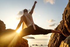 Grabb som gör yoga på solnedgången vid havet arkivfoton