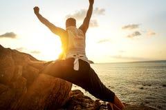 Grabb som g?r yoga p? solnedg?ngen vid havet arkivfoton
