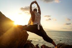 Grabb som g?r yoga p? solnedg?ngen vid havet royaltyfria foton