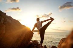 Grabb som g?r yoga p? solnedg?ngen vid havet royaltyfri foto