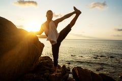 Grabb som g?r yoga p? solnedg?ngen vid havet royaltyfri bild