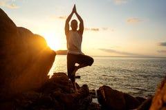 Grabb som g?r yoga p? solnedg?ngen vid havet royaltyfria bilder