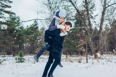 Grabb som ger hans flickvän ridtur på axlarna i unga älska par för vinterskog som har rolig det fria arkivfoto
