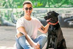 Grabb som kramar med hans hund labrador som spelar i parkera arkivbilder