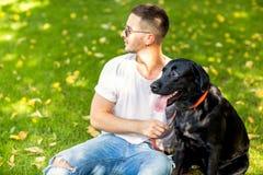 Grabb som kramar med hans hund labrador som spelar i parkera arkivbild