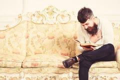 Grabb som läser den gamla boken med njutning Humoristiskt litteraturbegrepp Macho på att skratta framsidaläseboken uppsöka mannen royaltyfri foto