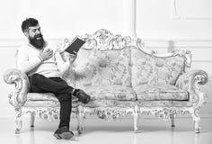 Grabb som läser den gamla boken med njutning Mannen med skägget och mustaschen sitter på den barocka stilsoffan, håll bokar, den  royaltyfria foton