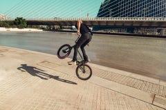 Grabb som lurar en bmxcykel ner gatan fotografering för bildbyråer