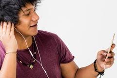 Grabb som lyssnar till spelaren mp3 på hans telefon Arkivbild