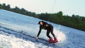Grabb som rusar längs skogsjön på rörande vattenyttersida för wakeboard vid handen stock video