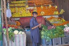 Grabb som säljer frukt i marknad Arkivbilder