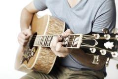 Grabb som spelar en akustisk gitarr Royaltyfri Bild
