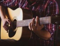 Grabb som spelar en akustisk gitarr på en anteckna studio arkivbilder