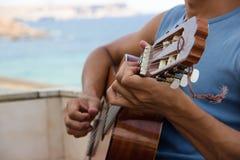 Grabb som spelar gitarren på en balkong på havet royaltyfri foto