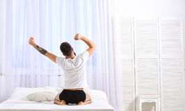 Grabb som sträcker armar som är fulla av energi i morgon Macho med skäggsträckning som kopplar av efter, ta sig en tupplur, vila  Arkivbild