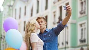 Grabb som tar selfie med den attraktiva blonda flickan som kysser honom, romantiskt datum, förälskelse Royaltyfria Foton