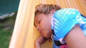 Grabb som utomhus sover i hängmatta utomhus- rekreation för lunch arkivfilmer