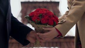 Grabb som visar hans affektion till flickvännen som framlägger kvinnan med buketten av rosor lager videofilmer