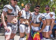 Grabbar för ` för amerikansk fotboll för ` på bögen Pride Parade arkivfoton