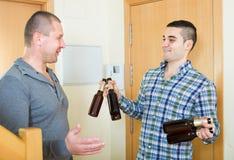 Grabbar med ölflaskor på dörröppningen arkivbild