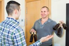 Grabbar med ölflaskor på dörröppningen fotografering för bildbyråer