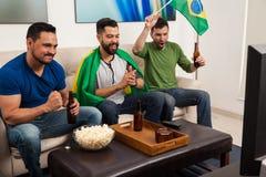 Grabbar som hurrar för Brasilien på TV Royaltyfria Bilder