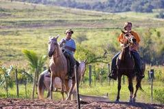 Grabbar som rider en häst Arkivfoto