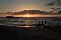 Grabbar som tar foto, medan hålla ögonen på solinställningen över ett härligt hav arkivbild