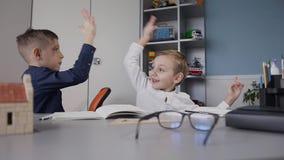 Grabbarna gjorde deras läxa, och gleefully plaskat i deras gömma i handflatan Barn sitter på skrivbordet hemma i arkivfilmer